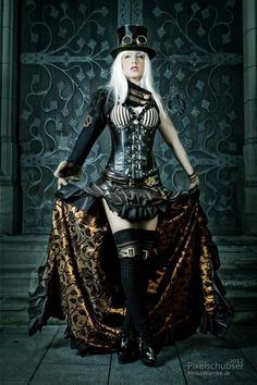Steampunk fashion photography. Top hat with monicals over the top, single sleeve jacket, & leather ruffle high skirt with the low showing detailed fabric pattern &  hardware buckles at her stockings.