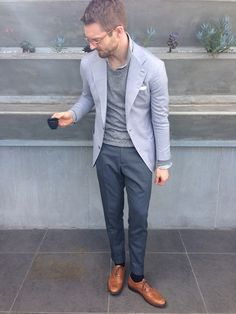 Pale greyish blue jacket, dusty grey trousers, and long sleeve light knit, white shirt and brown lace ups