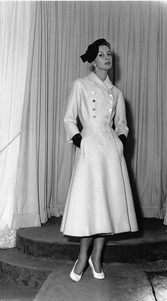 1955 Marie-Therese in double-breasted white wool coat with flared skirt by Pierre Balmain