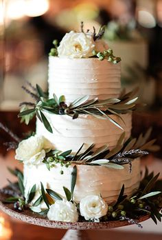 Classic white cake with a few white rose blooms and rustic garden greens