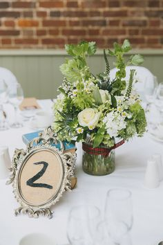 White Rose centrepieces & hessian framed table numbers |  Photography by http://www.mckinley-rodgers.co.uk/