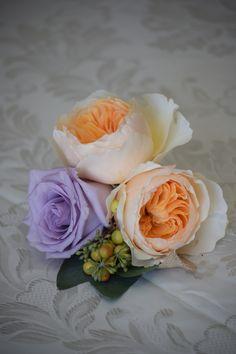 boutonniere made of dreamy peach garden roses, hypericum berry