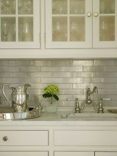 Glass-front upper cabinets and ivory lower cabinets paired with white marble…