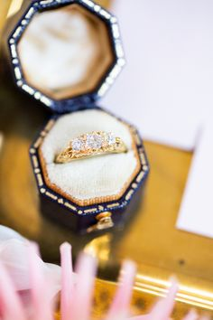 Held in this velvet ring box is our 18ct Yellow Gold and Diamond Victorian Style Engagement Ring. The ring has been expertly carved with an intricate scroll pattern. The three diamonds are Victorian/Old-cut diamonds which were typically used in this style of ring. Photographer: eleanorstenner.com; Stylist: thetimelessstylist.co.uk #victorianstyleengagementring #diamondengagementring #velvetringbox #threestoneengagementring #trilogyengagementring Victorian Engagement Rings, Three Stone Engagement Rings, Diamond Engagement Rings, Trilogy Engagement Ring, Three Stone Diamond Ring, Hatton Garden, Velvet Ring Box, Scroll Pattern, Victorian Fashion