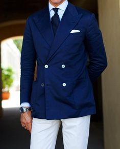 Navy double-breasted jacket, white shirt with blue stripes, navy tie, white pants