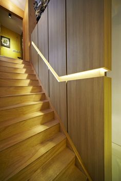 Stair Design Ideas - 9 Examples Of Built-In Handrails // In this Singaporean home, a wooden wall is broken up by the built-in handrail that features hidden lighting.