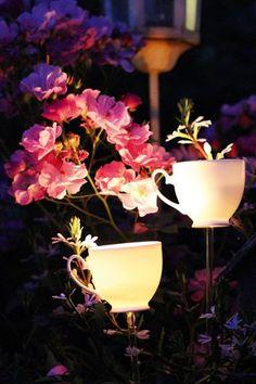 Charming tea-cups hold tea lights at an outdoor garden wedding