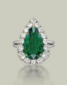 AN EMERALD AND DIAMOND RING BY HARRY WINSTON Set with a pear-shaped emerald in a brilliant-cut diamond surround mounted in platinum ring size 7 with ring sizer With maker's mark of Jacques Timey (indistinct) for Harry Winston
