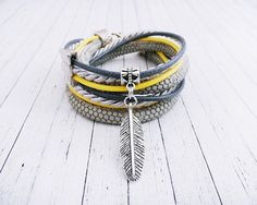 Great gift for best friend. Handmade bracelet made of cotton cords and eco strap. It is doubly wrapped around the wrist, and the whole adorned with feather pendant and spacer. Feather in Grey – a unique product by ilovehandmadeUK via en.DaWanda.com