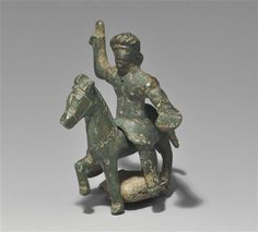 Celtic   Circa 1st century BC-1st century AD. A cast bronze two-piece horse-and-rider figurine comprising: cast bronze horse with one foreleg raised, head erect,mane represented by a line of incised strokes