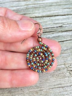 "Colorful and light weight beaded spiral earrings made of Czech glass seed beads in turquoise, olive, yellow, blue and red. Approx the size of quarter and 1.5"" in length."