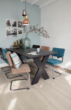 repeindre sa cuisine avec un mur en bleu pastel, et un mur en briques blanches, table noire avec les pieds en X, revetement du sol en couleur sable, plafond avec des poutres peintes en blanc