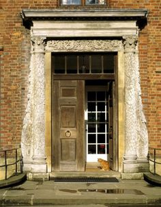The front door at Chartwell with the 18th-century carved wooden doorcase purchased from the London dealer Thomas Crowther. The cat is a recent reincarnation of Churchill's ginger cat Jock. ©National Trust Images/Rupert Truman