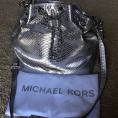 Michael Kors silver snake embossed leather bag Michael Kors silver snake embossed bucket bag, NWOT, dust bag included, silver, five pockets inside, one zip up, two straps, longer one is removable, hanging MK charm is removable. Michael Kors Bags Shoulder Bags