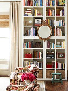 Mirror hung over bookshelves.