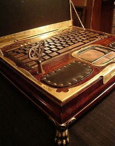Steampunk notebook In an elegant wooden box. Tthe keyboard and touchpad are made of copper. To create the design of the notebook, parts of an old clock was used. The computer starts using an old key, similar to the keys of a music box. Speaker holes look like a violin and are covered with black cloth. Hands can rest on upholstered leather..