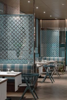 The decorative screens in this modern restaurant are used to create a separation between guests, allowing for a sense of privacy but at the same time allowing light to pass through.