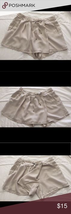 Khaki-taupe colored short/skirt This is a very unique piece of clothing! This is a taupe pair of shorts that looks like a pleated skirt in the front. The left short leg is a normal sized pair of shorts. The right short leg is looser which gives the illusion of the pleated skirt in the front. A beautiful, neutral piece that can be dressed up or dressed down. Perfect breezy fabric that feels very light in the spring and summertime. Mango Skirts Mini