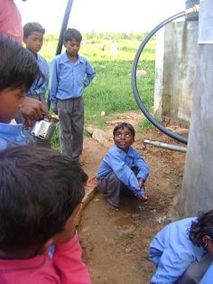 School children in India line up for drinking water from a solar-powered pipe project.