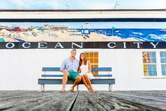 Couple sits on park bench in front of Ocean City sign on Jersey Shore boardwalk.   Bartlett Pair Photography   http://www.mywedding.com/articles/jessica-zachary-engagement-session/