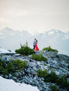 Engagement session in the snowy mountains with a red dress