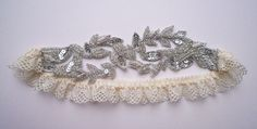 The Aphrodite garter combines stunning leaf embellishment & lace. This is a beautiful hand beaded piece....silver sequins, beads & metallic embroidered thread form this timeless design. Vintage with a modern twist. Designed by and exclusive to Florrie Mitton.    Perfect for the ultra stylish bride. Each Florrie Mitton garter is hand made in the U.K using the finest laces, silks, trimmings & carefully sourced vintage findings. All garters come presented in a beautiful gift box for you to…