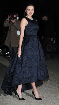 Miranda Kerr made her first appearance as the face of H&M in a gorgeous navy blue brocade gown, which she paired with black high heels and a diamond necklace. #mirandakerr #h&m