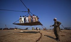 The Ship Breakers - In Focus - The Atlantic Laborers stand on a makeshift cable carriage which transports them onto a ship to separate it into scrap metal at Gaddani ship breaking yard on November 24, 2011. (Reuters/Akhtar Soomro)