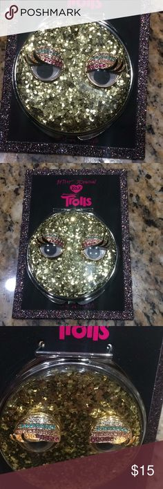 Betsey Johnson compact mirror Betsey Johnson compact mirror. From the Trolls collection at Macy's . Has gold glitter with a clear coat over it. Google eyes that are raised with crystals on top. Frame and back of compact are silver tone. Brand new Betsey Johnson Accessories