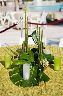 Monstera leaves and bamboo shoots are paired with tiny succulents for the outdoor wedding celebration.