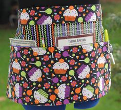 This 4 pocket apron is perfect for carrying everything you need while at a craft show, farmers market, in your studio, kitchen, garden, office, school, or work.    Halloween Cupcakes and Treats Pocket Vendor/Craft/Market/Waitress/Utility Apron    The apron is made with 100% cotton designer fabric, featuring a delicious Halloween cupcakes and treats fabric print. The fabric has a sparkle glitter in the fabric that makes it sparkle in the light. A wonderful Halloween apron t...