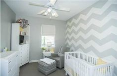 Light grey and white surround this space, with zig-zag stripe pattern on right wall, white wood crib and matching dressers, and grey armchair with matching ottoman.