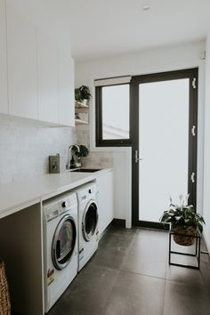 Gorgeous luxury laundry with marble brick splashback, large format grey floor tiles and loads of storage