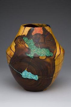 by Morrie Elmer   A master at his craft;  turning exotic woods into unusually shaped vessels and embellishing them with subtle touches of turquoise, coral and other natural stones.