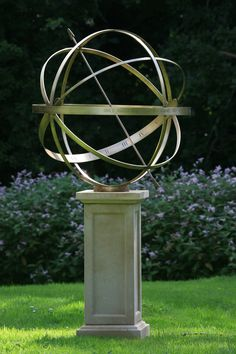 A large armillary looking great in front of a flower bed