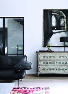 Black leather couch with silver metal accents, large mirror, and intricate wood design dresser
