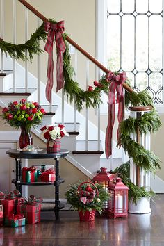 Fresh Christmas garland draped on the stairway banister makes for a dramatic and festive entryway.