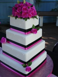 This 4 tiered cake is covered in white fondant, with royal icing dots. The hot pink and black ribbon help to accent each tier. The hot pink roses are sugar paste and give this cake an elelgant look.