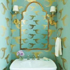 Plain eggshell paint can feel washed-out in tiny powder rooms; instead, take a risk with a bold, large-print wallpaper. It adds color and a whimsical feel, plus makes the space feel bigger overall. This one (by Abnormals Anonymous), printed with gilded puffer fish on a turquoise background, is sophisticated but playful with its undersea vibe.