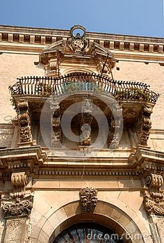Photo made at a particular of an elegant building in Ragusa in Sicily (Italy). In the image you see, the bottom of a typical Baroque balcony, the railing projecting wrought iron, the top of the door that looks like a chapel, then the cornice and the blue sky.