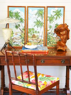 Writer's Desk:   A rattan chair and desk add to the tropical theme in the sunroom. The mix of vintage tropical artwork, a classic wood carving, and modern lamp add character to the rich wood desk.