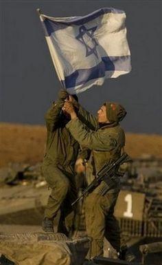 IDF soldiers raise Israeli flag.