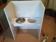 Dog water bowl station - something like this would work with a high one as pictured and then a shelf at the bottom for the smaller dogs...put on locking wheels so it can be tucked away in the laundry room on the weekends?