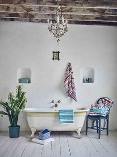 A bohemian styled bathroom with a free standing tub, a cactus planter, vibrant color pattern textiles and a blue chair is a real charmer. Image by Georgehome at ASDA.