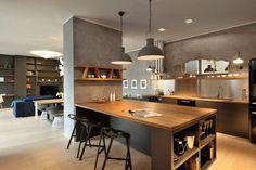 Mesa de madeira com base preta, mesa alta com banquetas, piso laminado de claro, parede com textura de cimento. Como Escolher Banquetas para Cozinha