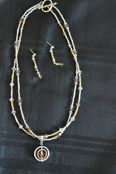 Double stranded silver and gold beads, gold and silver spacers and coordinating Swarovski crystal accents.  Pendant is a swiveling double silver and gold circle with a golden colored Swarovski crystal center.  23  Coordinating earrings-silver post dangles with additonal crystal drop.  9  $Sold