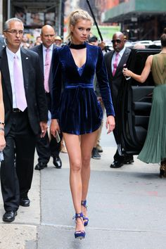 Stella Maxwell in a short blue velvet dress with long sleeves and a plunging neckline.