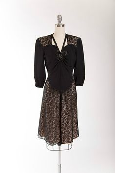 1940s vintage cocktail dress. Made of black rayon and black lace over a nude pink lining at the shoulders and skirt. Dress features cutout neckline with black sequined bow at sweetheart neckline. Orig