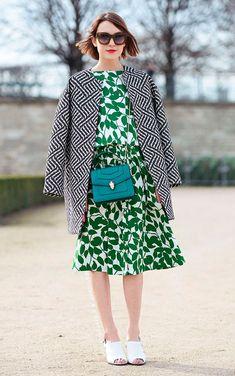 Street style look com casaco preto e branco, vestido midi verde estampado e sapato branco.