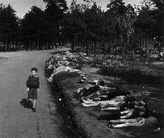 circa 20/4/1945 Sieg Maandag, giovane olandese sopravvissuto, cammina lungo una strada fiancheggiata di cadaveri